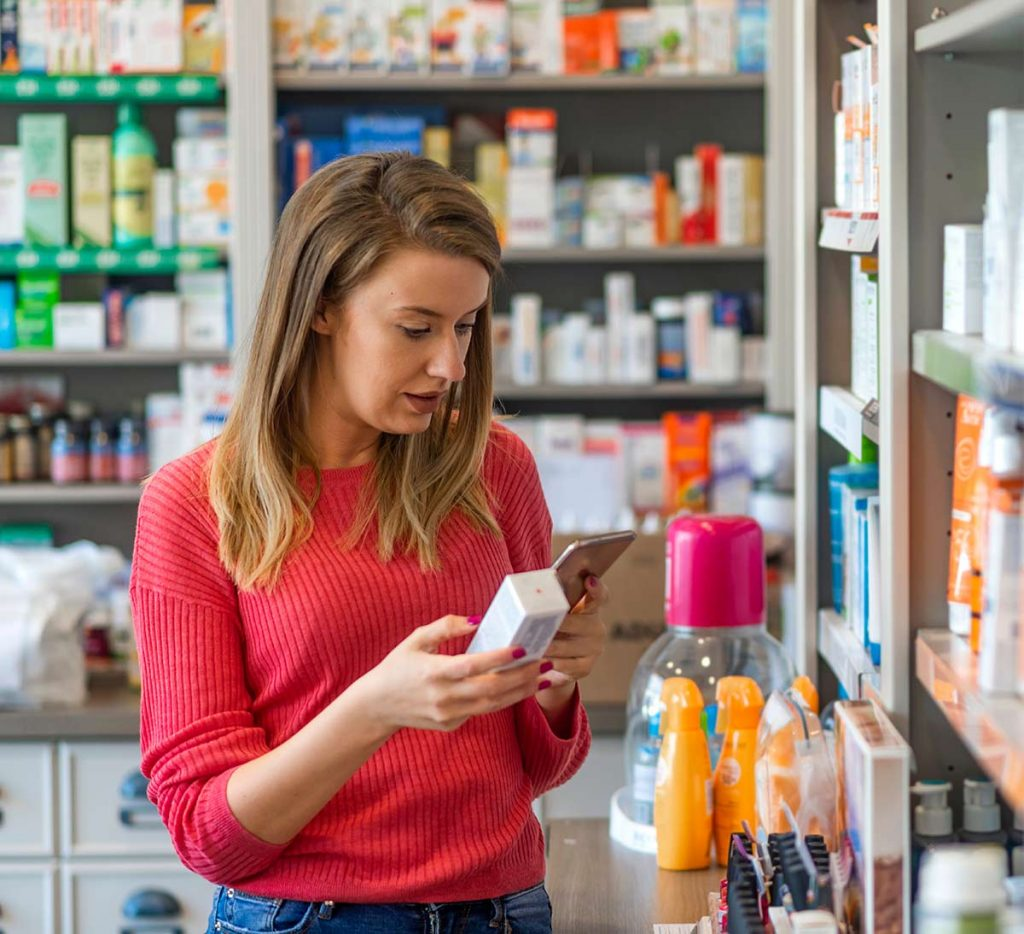 Plain language communications: woman reads medicines information in a pharmacy